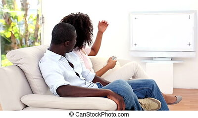 Couple watching tv on the couch at home in the living room