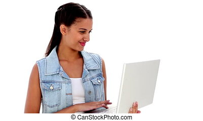 Pretty young brunette using laptop on white background