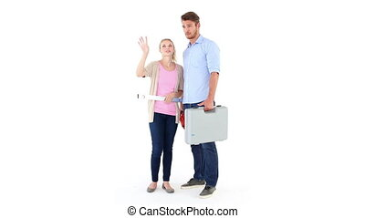 Happy young couple holding DIY tools on white background