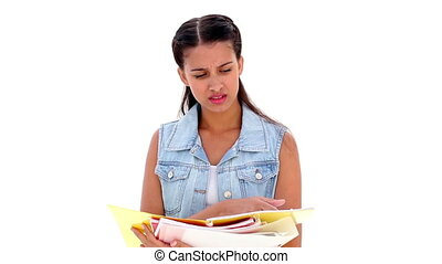 Pretty young student reading notes on white background