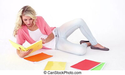 Pretty young student studying on floor on white background