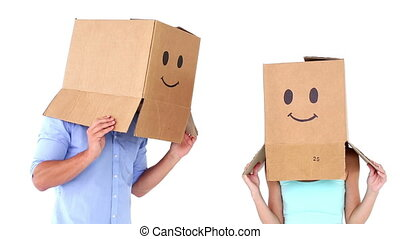 Young couple wearing emoticon boxes on heads on white...