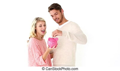Attractive young couple holding piggy bank on white...