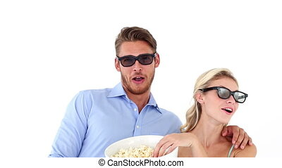 Attractive young couple watching a 3d movie on white...