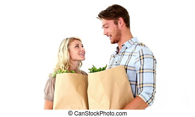 Attractive young couple holding grocery bags on white...