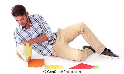 Handsome young student studying on floor on white background