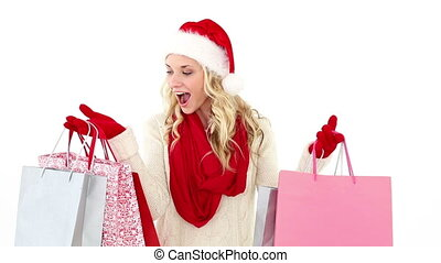 Festive young blonde holding shopping bags on white...