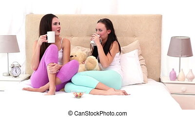 Pretty friends drinking coffee and talking at home in the...