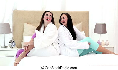 Pretty friends sitting on bed in bathrobes at home in the...