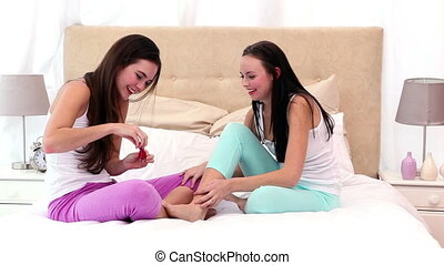 Pretty friends sitting on bed painting toenails at home in...