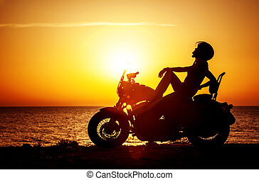 Woman biker enjoying sunset, female riding motorcycle,...
