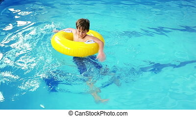 Cute little boy using inflatable ring in the pool at the...