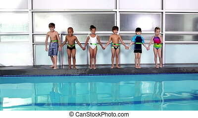 Cute children jumping into the pool together at the leisure...