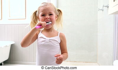 Cute little girl brushing her teeth at home in bathroom