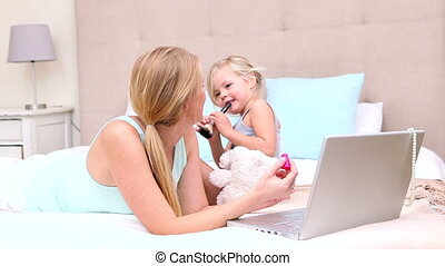 Mother and daughter lying on bed using laptop at home in...