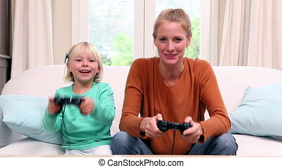 Cute little girl playing video games with her mother at home...