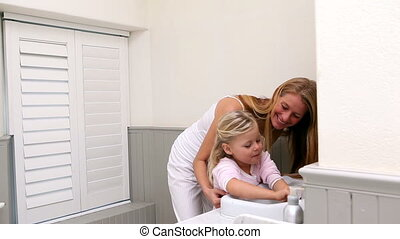 Cute little girl washing hands with her mother at home in...