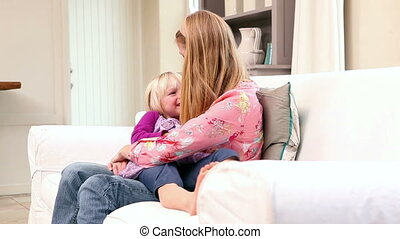 Cute little girl sitting with mother on the couch at home in...