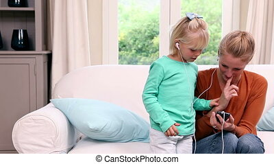 Cute little girl listening to music with her mother at home...