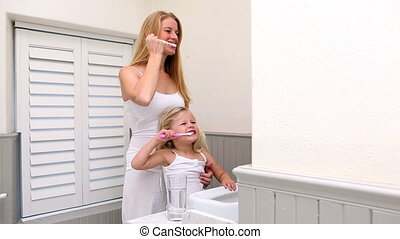 Cute little girl brushing her teeth with her mother at home...