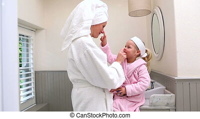 Mother and daughter putting face cream on at home in...