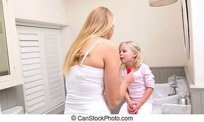 Mother putting lip gloss on little daughter at home in...