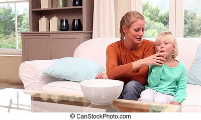 Cute little girl watching tv with her mother at home in...