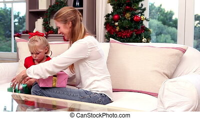 Mother and daughter exchanging gifts at christmas at home in...