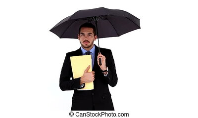 Young businessman holding a file under umbrella on white...