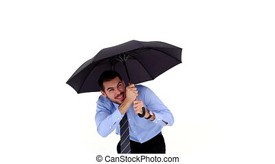 Young businessman sheltering with umbrella on white...