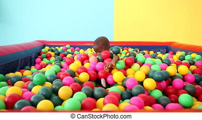 Cute little boy emerging from ball pool on blue and yellow...