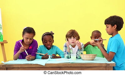 Cute pupils painting eggs for easter at the elementary...