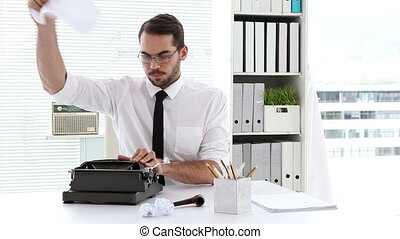 Businessman working on typewriter at his desk in his office