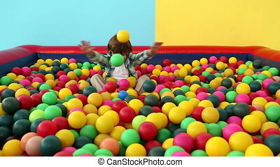 Cute little boy playing in ball pool on blue and yellow...