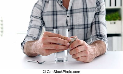 Casual businessman preparing dissovable painkiller in his...
