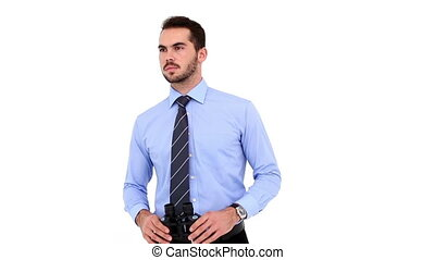 Young businessman looking through binoculars on white...