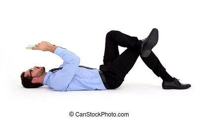 Businessman lying on floor and read