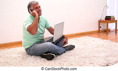 Mature man sitting on rug using laptop at home in the living...