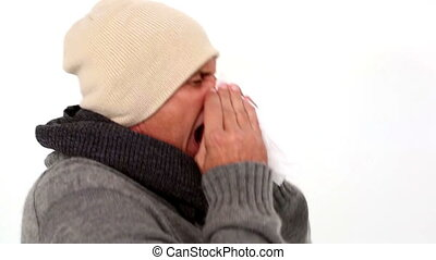Sick man in winter clothing sneezing on white background