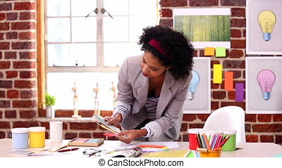 Pretty designer working at her desk in creative office