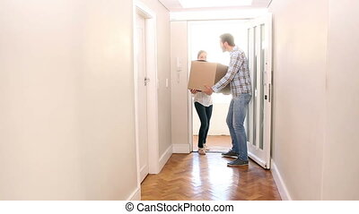 Attractive couple carrying cardboard box inside in their new...