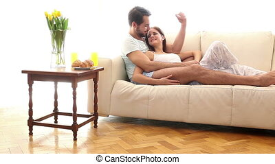 Attractive couple relaxing on the couch at home in the...