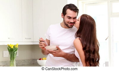 Attractive couple eating cereal in the morning at home in...