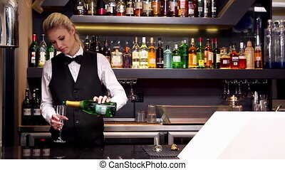 Attractive blonde pouring champagne at the bar at the...