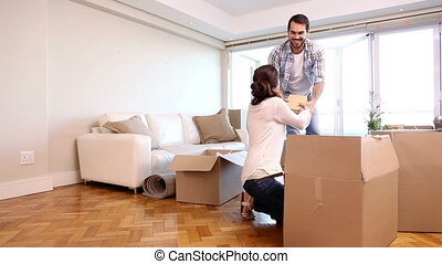 Attractive couple unpacking boxes in their living room in...