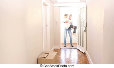 Attractive couple walking over the threshold in their new...