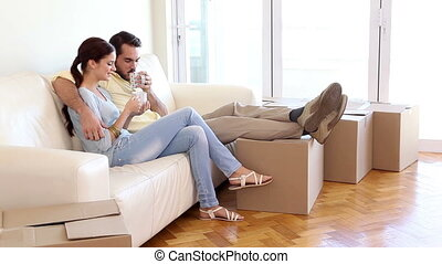 Attractive couple relaxing on couch in their new home