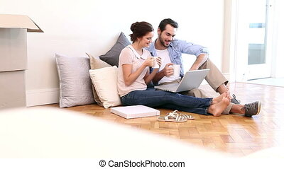 Attractive couple using laptop on the floor in their new...