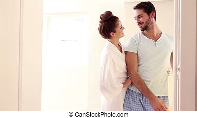 Attractive couple hugging with affection at home in the...