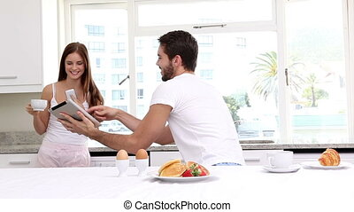 Attractive couple having breakfast together at home in the...